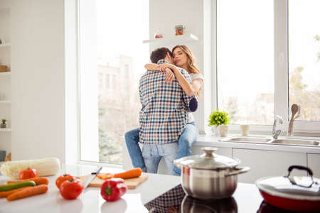 Close up photo pair beautiful he him his macho she her lady just married desire in love overjoyed hold each other hands bonding hugging touch lips kiss apartments flat bright kitchen room indoors Banque d'images