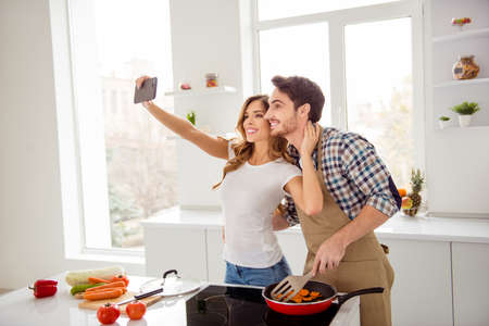 Close up side profile photo two people beautiful he him his macho she her lady telephone hands make take selfies make first breakfast dishes bonding apartments flat bright white kitchen room indoors