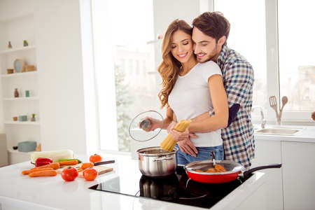 Close up photo pair in love beautiful he him his macho guy distracting she her lady just married honeymoon overjoyed make boil soup dish recipe bonding apartments flat bright kitchen room indoors 版權商用圖片