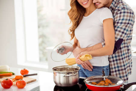 Cropped close up photo pair beautiful he him his macho guy distracting she her lady just married honeymoon overjoyed make boil soup dish recipe bonding apartments flat bright kitchen room indoors