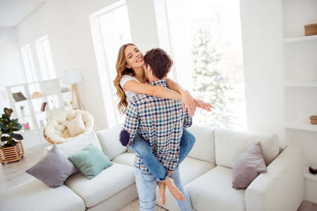 Nice attractive lovely lovable cheerful guy kissing seducing keeping wavy-haired lady life partners soulmates spending anniversary in light white style interior living room house Banque d'images - 123313971