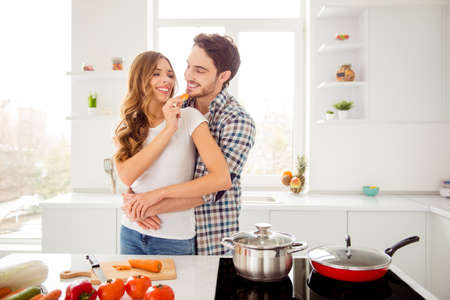 Close up photo pair beautiful he him his macho distracting hold waist hands she her feeding guy lady just married honeymoon overjoyed make breakfast bonding apartments flat bright kitchen indoors