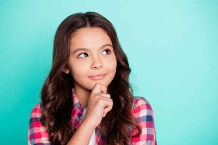 Close-up portrait of her she nice attractive lovely winsome sweet brainy clever wavy-haired pre-teen girl wearing checked shirt thinking touching chin isolated on bright vivid shine blue background