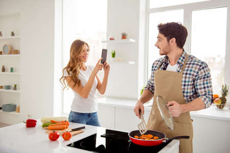 Close up photo two people beautiful he him his macho she her lady romance telephone hands master class blogger make video recipe for followers post apartments bright white kitchen room indoors Stock Photo