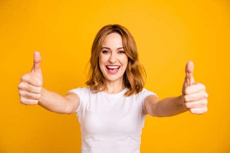 Nahaufnahme foto schön hübsch sie ihre foxy dame halten arme hände daumen finger hoch kurze frisur erstaunt aufgeregt beratung kaufen käufer neues produkt tragen lässiges weißes t-shirt isoliert gelber hintergrund