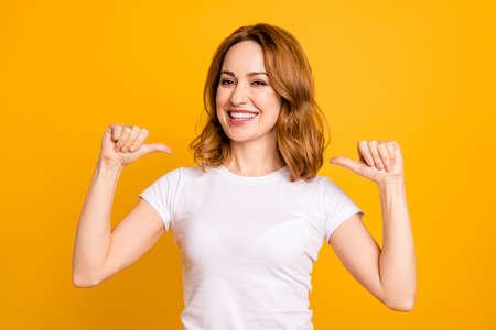 Gros plan photo incroyable belle elle ses pouces de dame indiquent la poitrine directe confiante à pleines dents Je suis le meilleur choix choisir choisir me sélectionner des conseils porter un t-shirt blanc décontracté isolé fond jaune