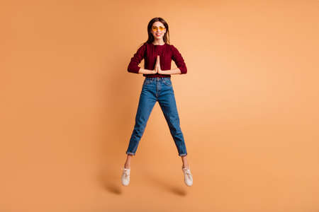 Full length body size photo beautiful she her lady jumping high hands arms together want help balance wear casual red burgundy knitted pullover denim jeans isolated pastel beige background