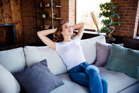 Portrait of her she nice-looking attractive lovable lovely pretty winsome charming cheerful cheery dreamy wavy-haired girl sitting on sofa having rest at industrial loft brick style interior room