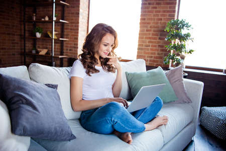 Profile side view portrait of her she nice-looking attractive cheerful wavy-haired girl sitting on comfortable divan browsing at industrial loft wooden brick style interior room hotel Banco de Imagens