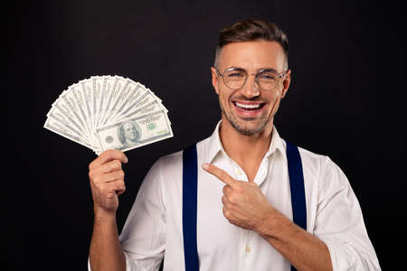 Close-up portrait of nice attractive cheerful guy wearing eyeglasses eyewear showing fan of usd 100 win winner lottery credit loan freelance savings deposit bank isolated on black background