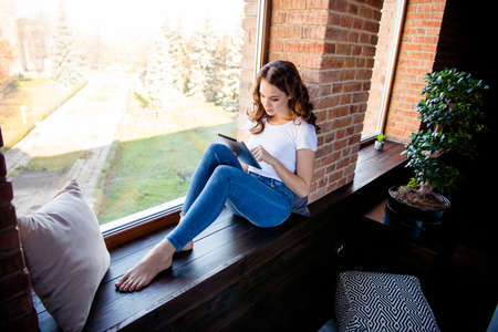 Nice-looking attractive lovely charming fit slim thin concentrated focused wavy-haired girl sitting on window sill reading ebook news at industrial loft wooden brick style interior indoors