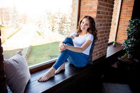 Porträt von ihr, sie sieht gut aus, attraktiv, hübsch, charmant, schlank, dünn, fröhlich, fröhliches, gewelltes Mädchen, das auf der Fensterbank im Innenbereich im Industrie-Loft-Holzziegel-Stil sitzt Standard-Bild