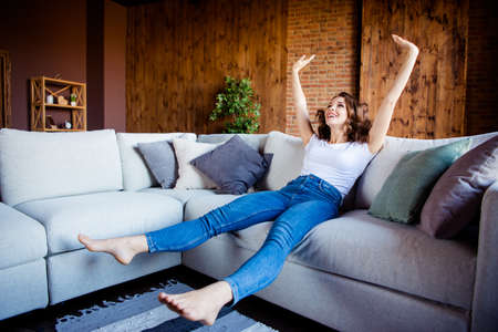 Full length body size view of her she nice attractive lovely charming cheerful cheery wavy-haired girl sitting on comfortable divan having fun time at industrial loft wooden brick style interior