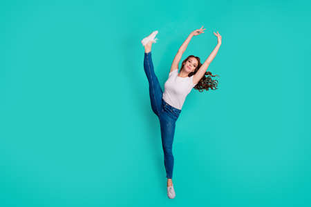 Full length body size view of nice attractive lovely graceful sportive slim fit thin adorable wavy-haired lady flexing practicing raising leg hands up isolated on bright vivid shine blue background