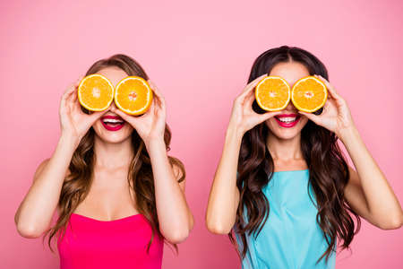 Close up photo two people beautiful she her ladies hands arms hold hide eyes specs organic nature fruits party festive chill hang out wear colorful dresses formal-wear isolated pink bright background
