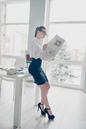 Vertical full length side profile body size photo she business lady eyewear eyeglasses hands arms fresh press reader article partnership company wear specs formal-wear white shirt skirt bright office Banco de Imagens