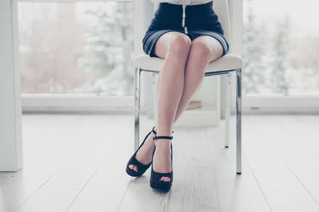 Cropped close up photo beautiful she her business lady folded legs hips sitting comfy cozy chair under table ideal soft shiny tender skin wear formal-wear white shirt black skirt modern bright office