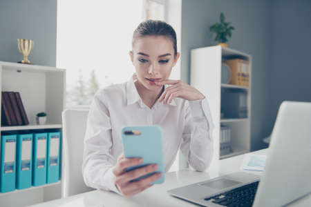 Close up photo beautiful she her business lady look wondered app screen hands arms telephone excited skype speak tell boyfriend notebook table wear specs formal-wear white modern bright office