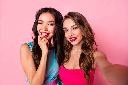 Dos hermosas mujeres tomando autofotografía sobre fondo vivo rosa rosa
