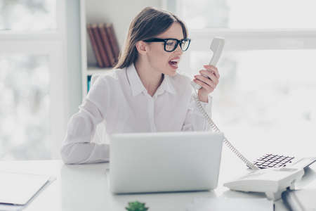 Close up photo beautiful yelling she her furious mad angry receiver online currency answer operator business chat notebook table sit bright light office wear specs formal-wear white shirt