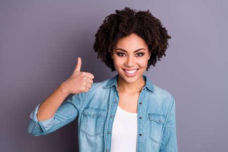 Retrato de linda dama positiva joven anunciar elección decisión aprobar de acuerdo punta venta noticias descuento sentirse contento contenido jeans vestido aislado fondo gris