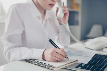 Cropped close up photo beautiful she her business lady pen pencil make notes notepad organizer listen important talk boss chief instruction notebook table bright office wear formal-wear white shirt