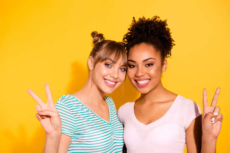 Close up photo beautiful diversity she her lady buddies fellows different nationalities hold hands arms show v-sign wear casual white striped t-shirt clothes outfit isolated yellow bright background