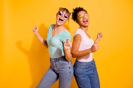 Cerrar foto hermosa gracioso ella su dama fiesta chicos manos brazos levantados movimiento moderno diferentes nacionalidades usan especificaciones de sol casual camiseta a rayas blancas ropa aislado fondo amarillo brillante Foto de archivo