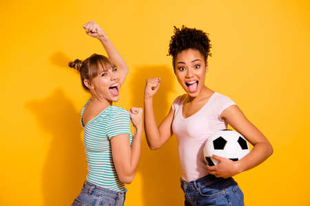 Portrait cheerful student hold hand energy achieve raise fist beautiful bun scream yes goal success sporty champions wavy curly hairdo top-knot trendy style stylish t-shirt isolated yellow background
