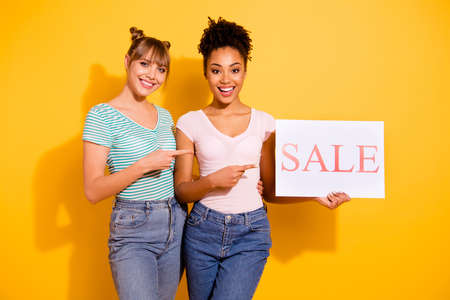 Portrait of positive cheerful satisfied people hipster content hold hand advise choice indicate ad wavy curly haircut top-knot trendy style stylish t-shirt jeans isolated on yellow background
