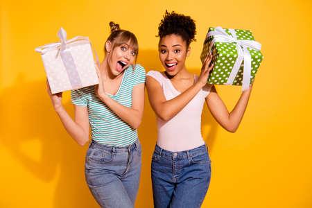 Nahaufnahme Foto fröhliche Studentin halten Hand großes Geschenk Jubiläum schreien Inhalt freuen sich erstaunt unerwartete gewellte lockige Haarschnitt Top-Knot-Brötchen trendiger Stil stilvolle T-Shirt Jeans isoliert gelber Hintergrund Standard-Bild