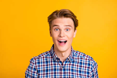 Close up photo amazing youngster he him his man excited not believe eyes achievement perfect styling ready for new beginning wear casual plaid checkered shirt outfit isolated yellow bright background.
