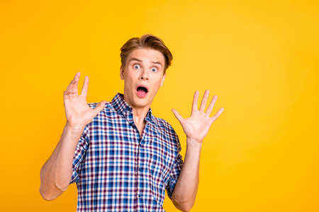 Close up photo amazed he him his man mouth open eyes full fear oh no facial expression hands arms raised air ask stop wear casual plaid checkered shirt outfit isolated yellow bright background.