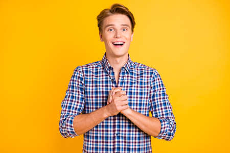 Portrait of his he nice-looking attractive delighted cheerful cheery glad guy wearing checked shirt hoping luck isolated over bright vivid shine yellow background. 写真素材