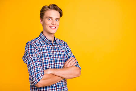 Close up side profile photo amazing youngster he him his man excited showing white ideal teeth arms crossed bossy look wear casual plaid checkered shirt outfit isolated yellow bright background.