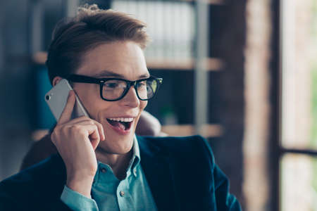 Close up photo positive cheerful satisfied cute guy have device use user dialogue friends family free time enjoy excited rejoice eyeglasses eyewear jacket stylish trendy industrial interior.