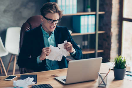 Portrait negative depressed frustrated guy hold hand paper work shred want shout sheets development use user laptop wrong decision solution decide choose choice stylish trendy suit interior industrial.