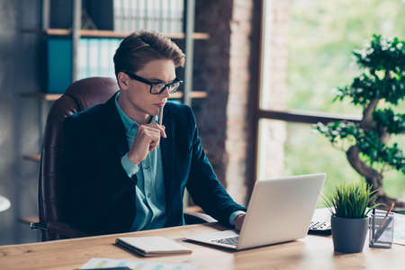Portrait of handsome charming entrepreneur sit table desk top use user pc modern technology have data presentation research wear black jacket suit touch chin pen industrial studio loft. Фото со стока