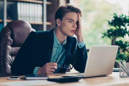 Portrait of negative guy feel ill sick have tension difficult decision choose solve solution choice use user modern technology tension migraine style stylish jackets sit desk interior industrial.