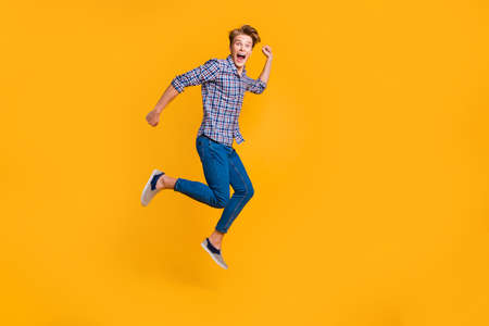 Full length body size view portrait of nice attractive cheerful cheery optimistic guy in checked shirt having fun running fast hurry rush isolated over bright vivid shine yellow background. Фото со стока