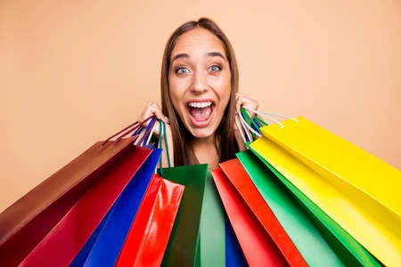 Close-up portrait of nice tanned fascinating attractive lovely cheerful cheery crazy glad straight-haired lady holding in hands bags with new clothes clothing isolated on beige pastel background. Stockfoto
