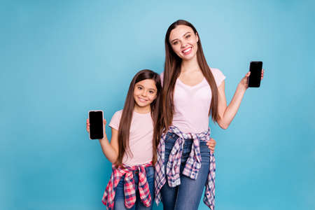 Portrait of two nice cute charming attractive lovely winsome cheerful cheery straight-haired girls showing device black display isolated on bright vivid shine green blue turquoise background