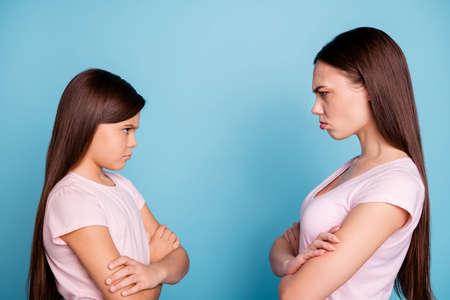 Nahaufnahme-Profilseitenansicht-Porträt von zwei attraktiven bösen Wut irritiert verärgert verärgert glatthaarige Mädchen sind nicht einverstanden mit gefalteten Armen einzeln auf hell leuchtendem, grün-blauem türkisfarbenem Hintergrund