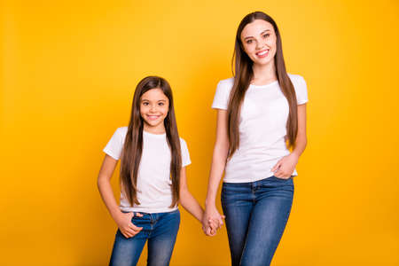 Close up photo two beautiful her she diversity lady different age best buddies hold hands arms go secondary highschool wear casual white t-shirts jeans denim clothes isolated yellow bright background