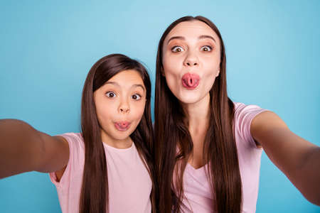 Self-portrait of two nice cute charming attractive crazy girlish cheerful comic childish straight-haired girls having fun time good mood isolated on bright vivid shine green blue turquoise background