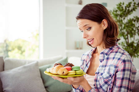 Portrait of cute charming lady astonished impressed incredible unbelievable unexpected pastry hold hand plate dish confectionery dressed checkered shirt outfit apartment