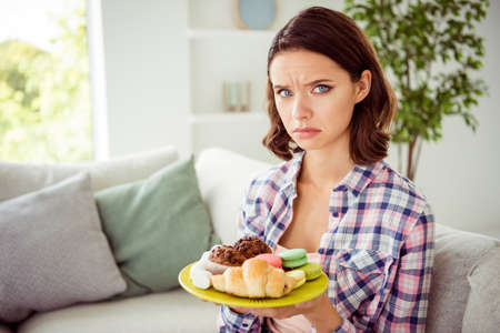 Close up photo of disappointed sad lady sit divan have free time rest hold hand variety confectionery pastry frown stylish trendy checked shirt outfit wavy curly hairstyle hairdo room apartment