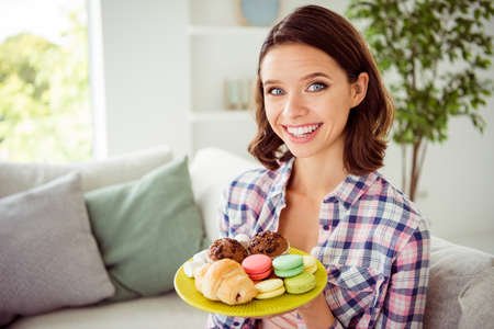 Close up photo charming nice pretty teen teenager hold hand plate pastry sugary variety products feel positive cheerful content satisfied wavy curly haircut style stylish trendy plaid shirt apartment Reklamní fotografie