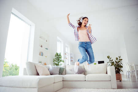 Full length body size low angle view photo nice cute funky funny hipster people hold hand device dance fool careless free time wavy curly hairdo stylish trendy plaid shirt jeans room apartment 免版税图像