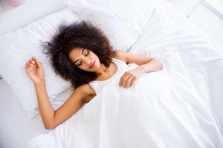 Gros plan au-dessus de la photo en grand angle belle elle sa peau foncée dame vacances réveil sain rêver yeux fermés samedi draps blancs vêtements de nuit confort couché grande chambre maison à l'intérieur